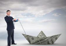 Homme d'affaires tirant le bateau du dollar de monnaie fiduciaire Photographie stock