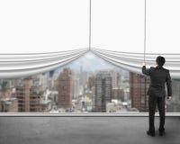Homme d'affaires tirant le rideau blanc vide ouvert avec le buil de ville de vue Images libres de droits