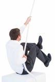 Homme d'affaires tirant une corde avec l'effort photos stock