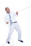 Homme d'affaires tirant une corde avec l'effort photos libres de droits