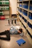 Homme d'affaires tombé avec le dossier dans la salle d'entreposage Photographie stock libre de droits