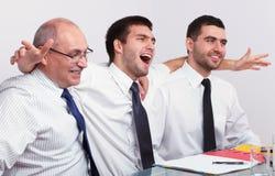 Homme d'affaires très heureux trois au cours du contact Images stock