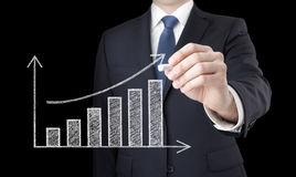 Homme d'affaires traçant un diagramme croissant Image stock