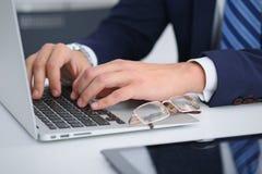 Homme d'affaires travaillant à côté de la dactylographie sur l'ordinateur portable Équipez les mains du ` s sur le carnet ou l'ho Images stock