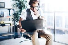 Homme d'affaires travaillant à son comprimé numérique se tenant dans des mains Homme élégant utilisant le casque audio et faisant Image libre de droits