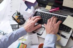 Homme d'affaires travaillant à un bureau encombré et malpropre image stock