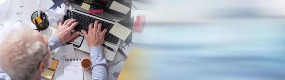 Homme d'affaires travaillant à un bureau encombré et malpropre image libre de droits