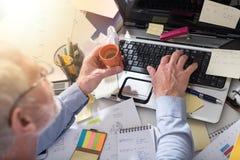 Homme d'affaires travaillant à un bureau encombré et malpropre, effet de la lumière image stock