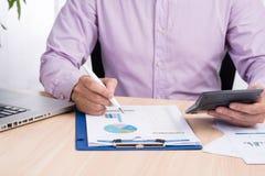 Homme d'affaires travaillant à un bureau Travaillent en indépendants le bureau de travail à la maison Note d'écriture sur un livr Images libres de droits