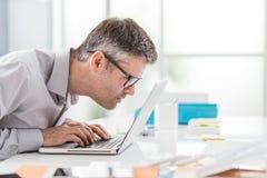 Homme d'affaires travaillant au bureau, il regarde la fin d'écran d'ordinateur portable et tient fixement ses verres, problèmes d images libres de droits
