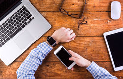 Homme d'affaires travaillant au bureau utilisant la montre intelligente Photo stock