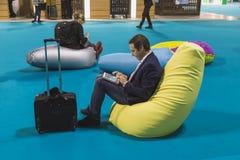 Homme d'affaires travaillant au comprimé au peu 2015, échange international de tourisme à Milan, Italie Images stock