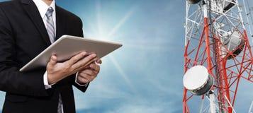 Homme d'affaires travaillant au comprimé numérique, avec le réseau de télécom d'antenne parabolique sur la tour de télécommunicat Image stock