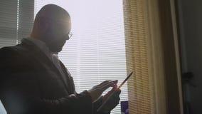 Homme d'affaires travaillant au comprimé numérique près de la fenêtre dans le bureau Homme à l'aide de la tablette digitale banque de vidéos
