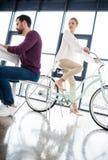Homme d'affaires travaillant au lieu de travail dans le bureau, femme faisant du vélo derrière Image stock