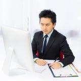 Homme d'affaires travaillant avec l'ordinateur de bureau photographie stock libre de droits