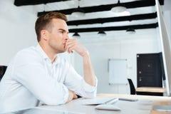 Homme d'affaires travaillant avec l'ordinateur et pensant sur le lieu de travail images stock