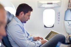 Homme d'affaires travaillant avec l'ordinateur portable sur l'avion Image stock
