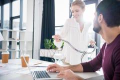 Homme d'affaires travaillant avec l'ordinateur portable sur le lieu de travail dans le bureau, femme faisant du vélo derrière Image stock