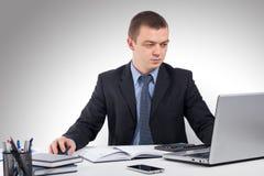 Homme d'affaires travaillant avec les documents et l'ordinateur portable Image stock