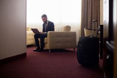 Homme d'affaires travaillant dans la chambre d'hôtel Image stock