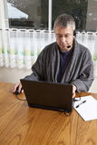 Homme d'affaires travaillant de la maison dans des pyjamas Photo stock