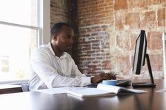 Homme d'affaires travaillant sur l'ordinateur dans le bureau images stock