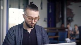 Homme d'affaires travaillant sur l'ordinateur portable à côté de la table Un jeune homme avec des verres ressemble à un hippie Re clips vidéos