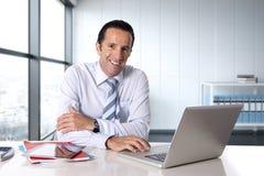 Homme d'affaires travaillant sur l'ordinateur portable d'ordinateur se reposant au bureau semblant sûr Images stock