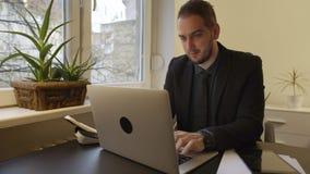 Homme d'affaires travaillant sur l'ordinateur portable dans le bureau prenant des notes sur le comprimé satisfait des résultats banque de vidéos