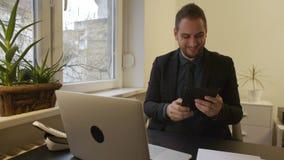 Homme d'affaires travaillant sur l'ordinateur portable dans le bureau prenant des notes sur le comprimé satisfait des résultats clips vidéos