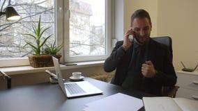Homme d'affaires travaillant sur l'ordinateur portable dans le bureau prenant des notes faisant l'appel téléphonique satisfait de banque de vidéos