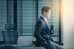 Homme d'affaires travaillant sur l'ordinateur portable dans le bureau, tenant une tasse de café photos stock