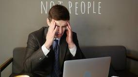 Homme d'affaires travaillant sur l'ordinateur portable en café l'homme d'affaires est bouleversé banque de vidéos