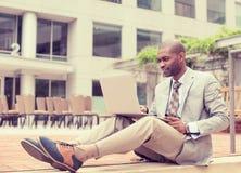 Homme d'affaires travaillant sur l'ordinateur portatif à l'extérieur Images stock