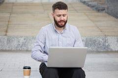 Homme d'affaires travaillant sur l'ordinateur portatif ? l'ext?rieur photos stock