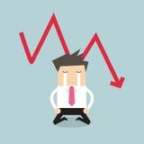 Homme d'affaires triste pleurant avec tomber vers le bas crise financière de graphique rouge de flèche Photographie stock libre de droits