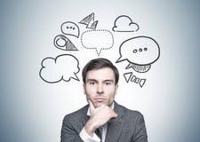 Homme d'affaires d'une chevelure foncé réfléchi, bulles de la parole Photo libre de droits