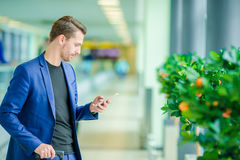 Homme d'affaires urbain parlant au téléphone intelligent à l'intérieur dans l'aéroport Veste de port de costume de jeune garçon o Image libre de droits