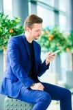 Homme d'affaires urbain parlant au téléphone intelligent à l'intérieur dans l'aéroport Veste de port de costume de jeune garçon o Images libres de droits