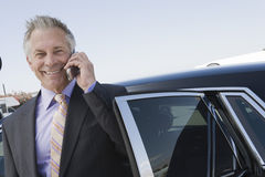 Homme d'affaires Using Cellphone Standing en la voiture Photos libres de droits