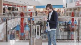 Homme d'affaires Using Digital Tablet dans le salon de départ d'aéroport Jeune indépendant avec la valise de laggage dans la zone Photos stock