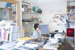 Homme d'affaires Using Landline Phone dans le siège social photographie stock