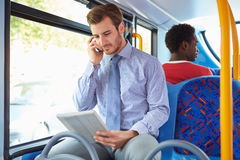 Homme d'affaires Using Mobile Phone et Tablette de Digital sur l'autobus Images stock