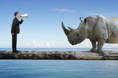 Homme d'affaires utilisant l'orateur hurlant au rhinocéros sur en bois simple Photographie stock libre de droits