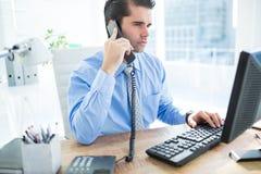 Homme d'affaires utilisant l'ordinateur et téléphoner photos stock