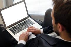 Homme d'affaires utilisant l'ordinateur portable à la maison photos stock