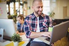 Homme d'affaires utilisant l'ordinateur portable au bureau créatif image stock