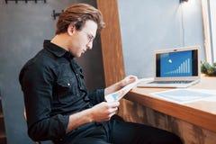 Homme d'affaires utilisant l'ordinateur portable avec le comprimé et stylo sur la table en bois dans le café avec une tasse de ca Image stock