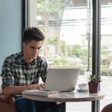 Homme d'affaires utilisant l'ordinateur portable avec le comprimé et stylo sur la table en bois dedans Image stock